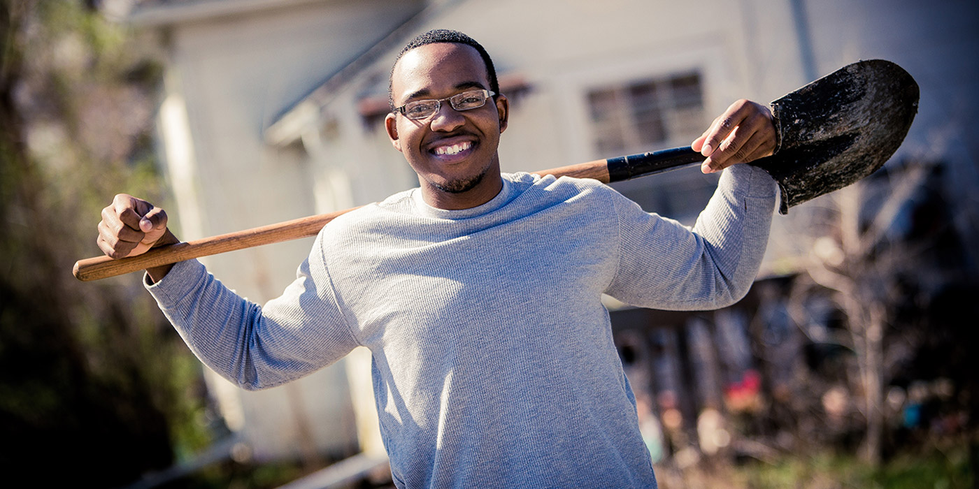 Student holding a shovel as part of a community project
