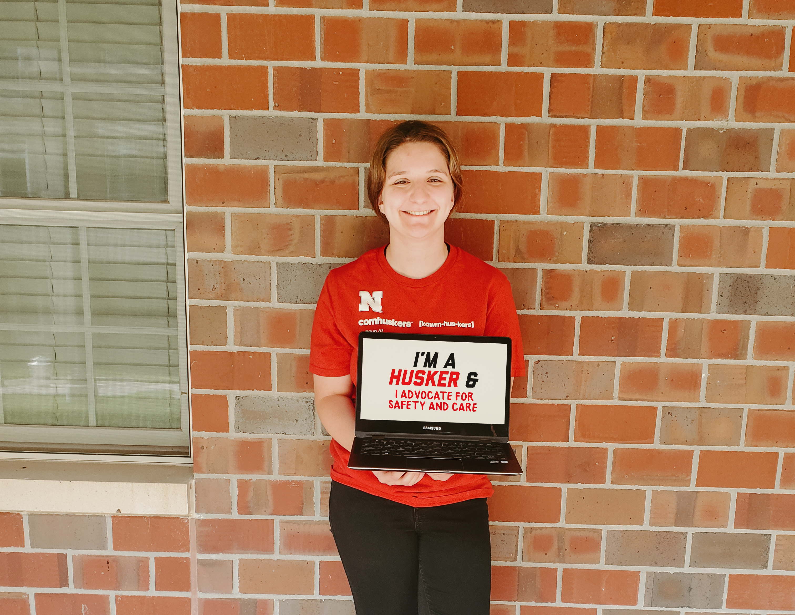 """Bianca holding a sign that says """"I'm a Husker and I advocate for safety and care."""""""