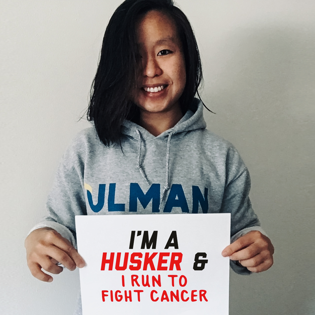 "Han holding a sign that says ""I'm a Husker and I run to fight cancer."""