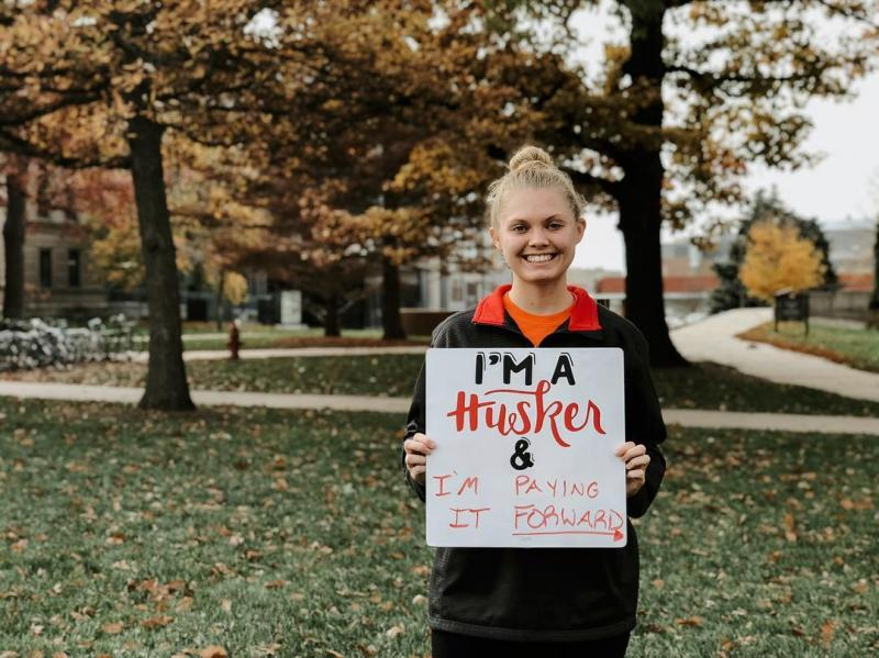 Student holding sign with I am a Husker language