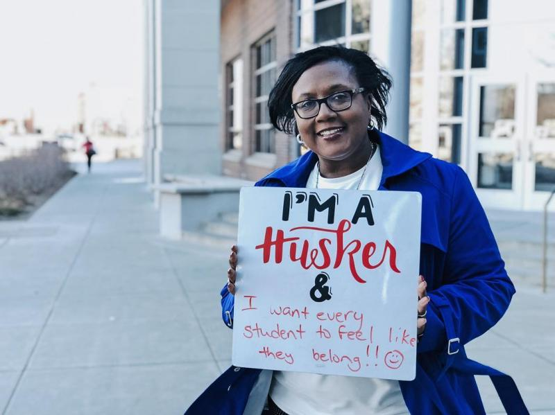 Staff member holding sign with I am a Husker language