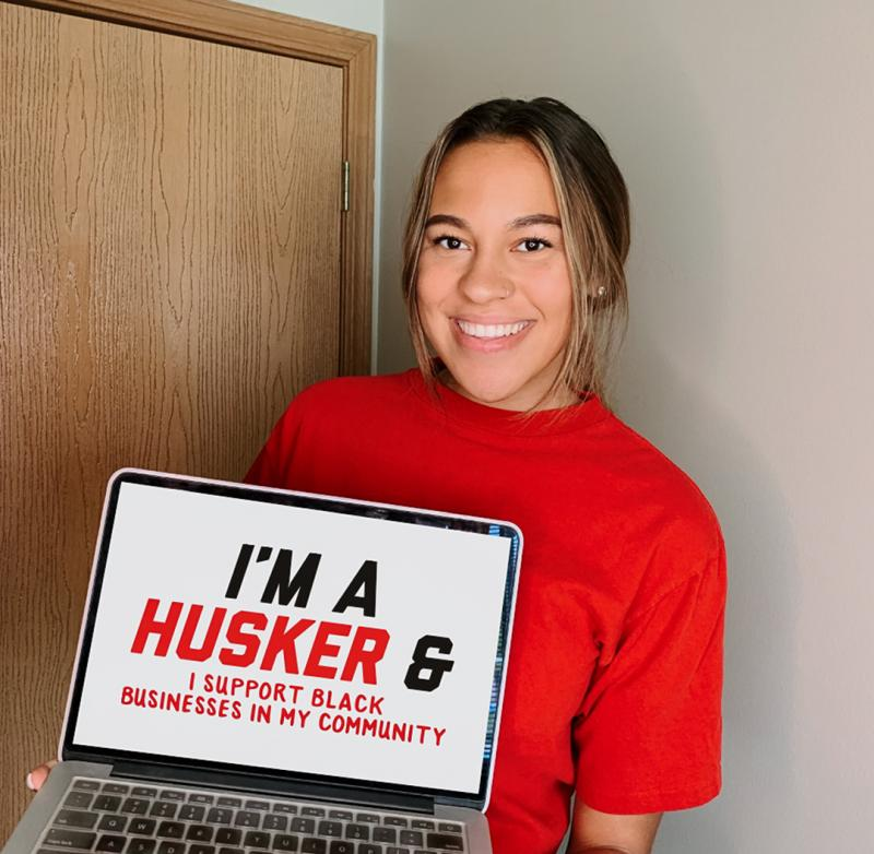 """Alexis holding a sign that says """"I'm a Husker and I support Black businesses in my community."""""""