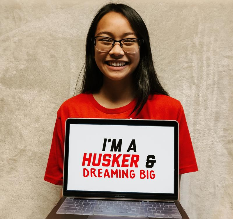 """Aliyah holding a sign that says """"I'm a Husker and dreaming big."""""""