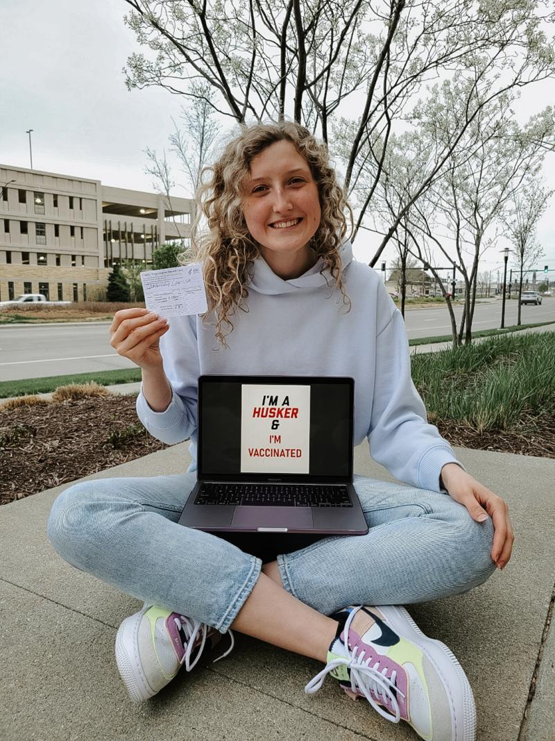 """Carissa holds her vaccination card and a computer that says """"I'm a Husker & vaccinated"""""""