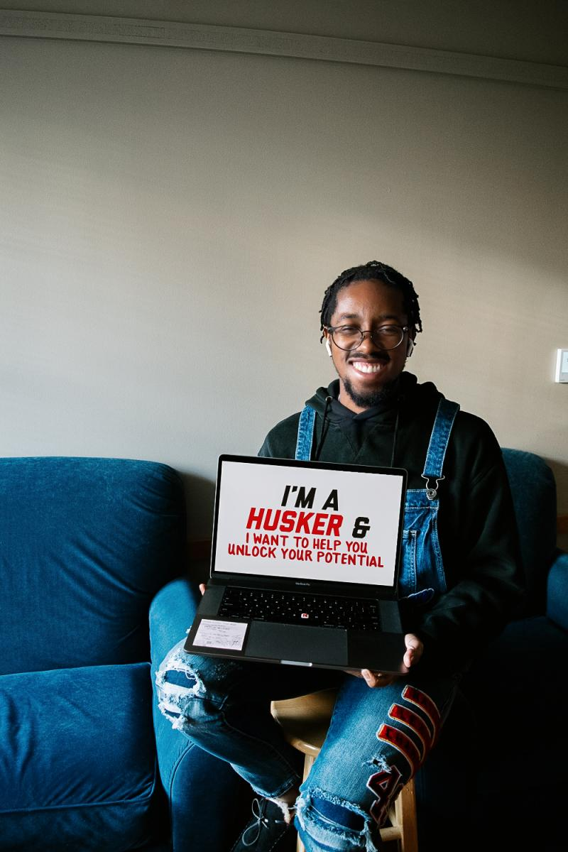 """Eric holding a sign that says """"I'm a Husker and I want to help you unlock your potential."""""""