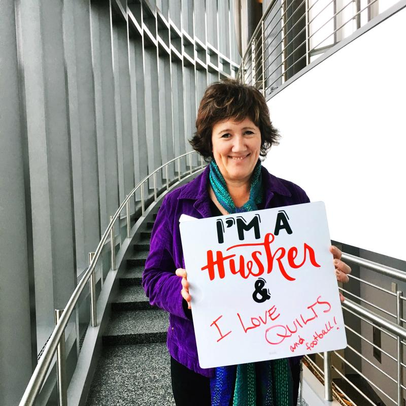 Staff holding sign with I am a Husker language