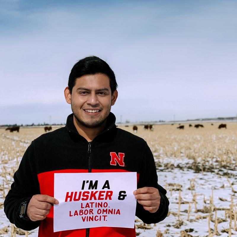 """Henry smiles for the camera with the Sandhills in the background. His sign says """"I'm a Husker & Latino. Labor Omnia Vincit."""""""