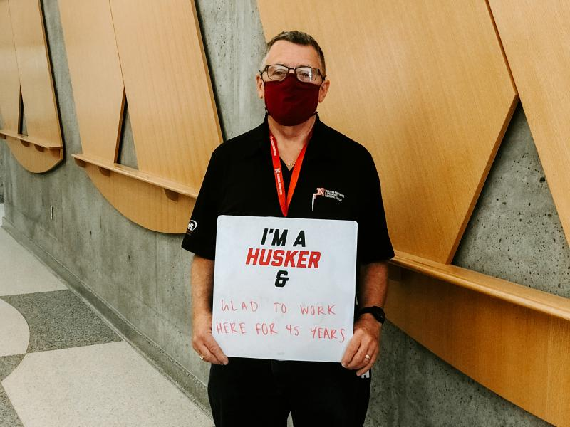 """Don holding a sign that says """"I'm a Husker and glad to work here for 45 years."""""""