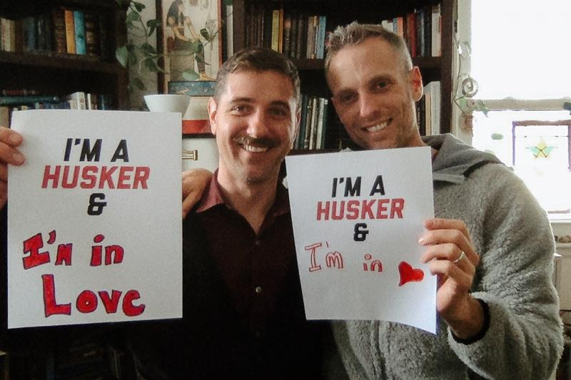"""Jim and Tim smile for the camera at home, both holding signs that say """"I'm a Husker & in love"""""""