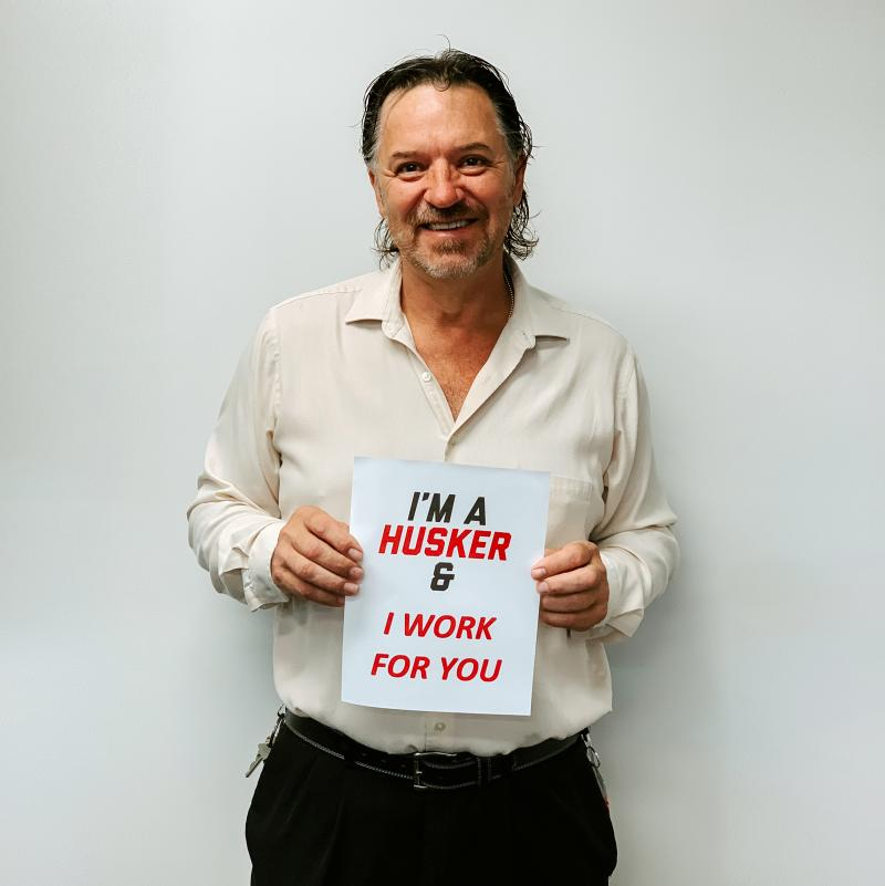 """Jim holding a sign that says """"I'm a Husker and I work for you."""""""
