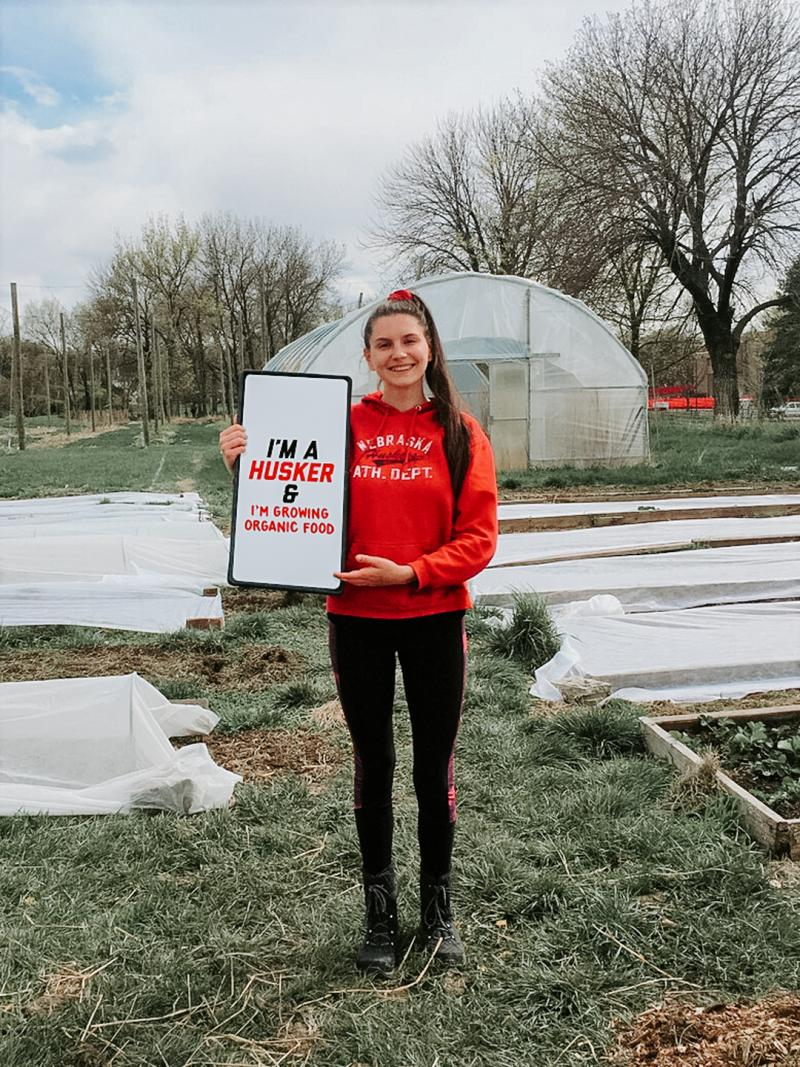 """Kat stands on the Student Organic Farm holding a sign that says """"I'm a Husker & I'm growing organic food"""""""