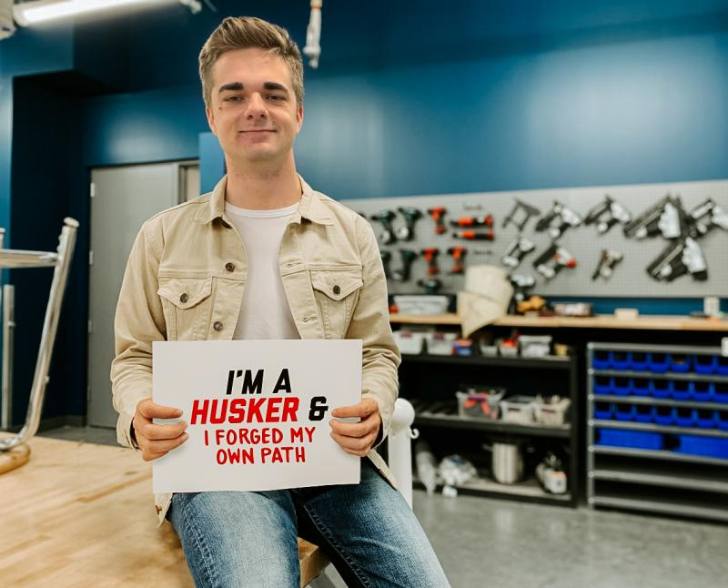 """John holds a sign that says """"I'm a Husker & I forged my own path"""""""