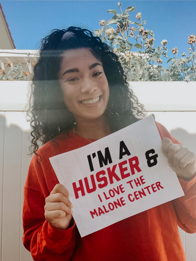 """Kami holding a sign that says """"I'm a Husker and I love the Malone Center."""""""
