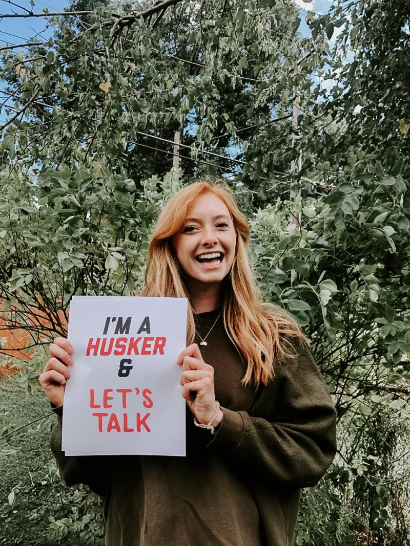 """Kari holding a sign that says """"I'm a Husker and let's talk."""""""
