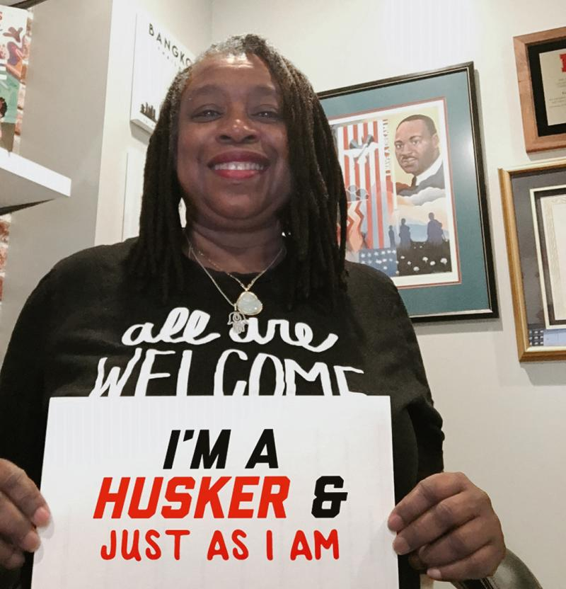"""Karen smiles for the camera holding a sign that says """"I'm a Husker & just as I am"""""""