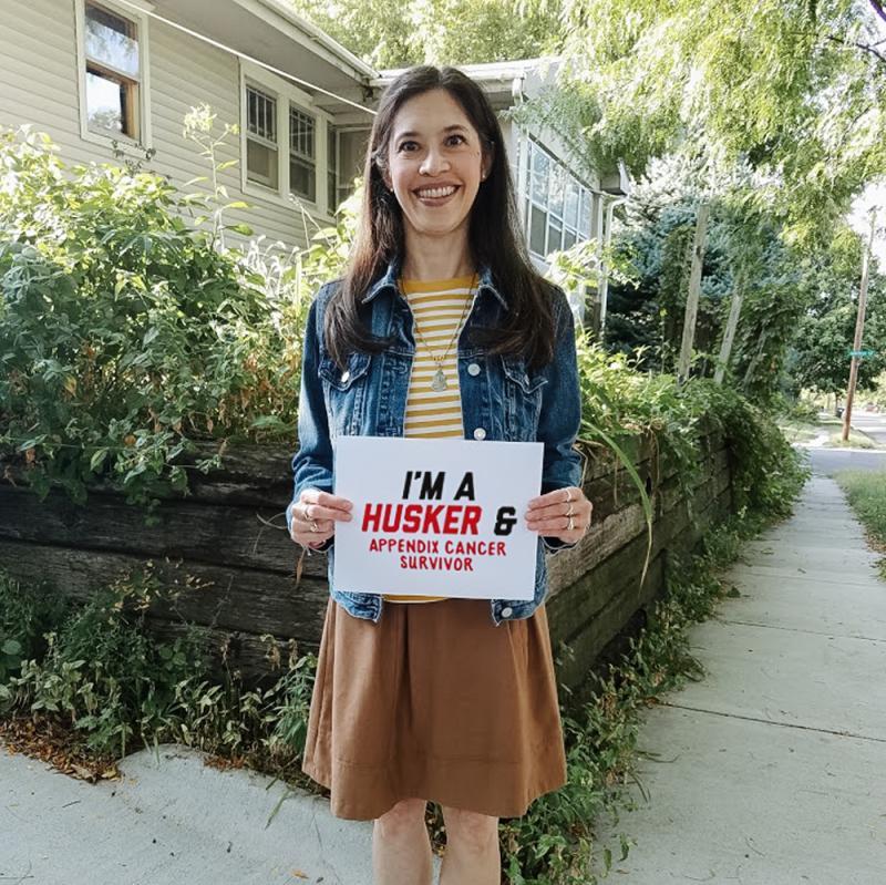 """Karen holding a sign that says """"I'm a Husker and appendix cancer survivor."""""""