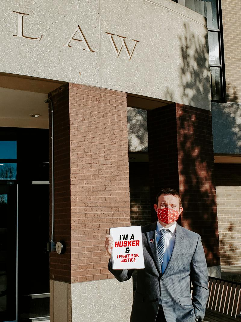 """Ryan stands outside the College of Law with a sign that says """"I'm a Husker & I fight for justice"""""""