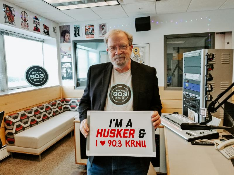 """Rick smiles for the camera in the KRNU studio. He holds a sign that says """"I'm a Husker & I love 90.3 KRNU"""""""