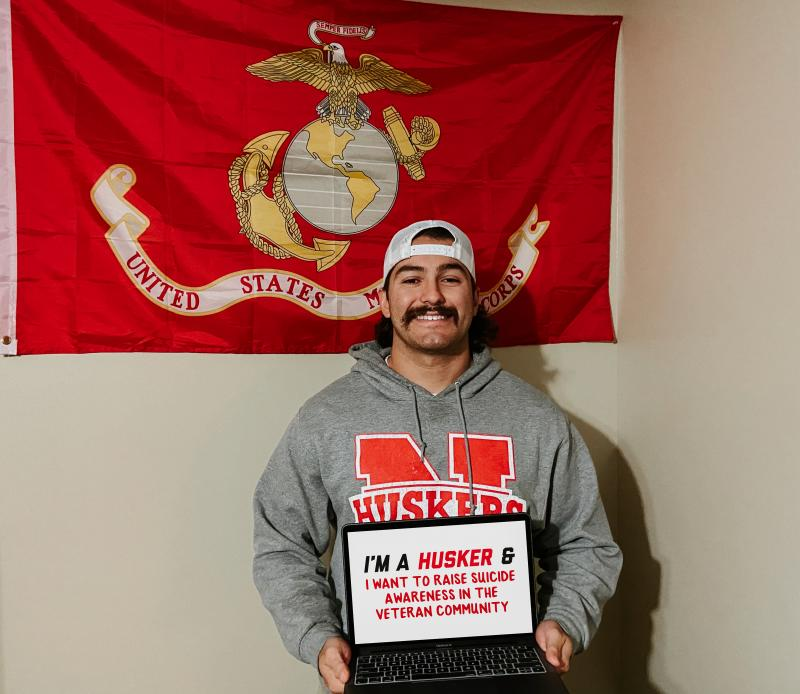 """Rodrigo holding a sign that says """"I'm a Husker and I want to raise suicide awareness in the veteran community."""""""