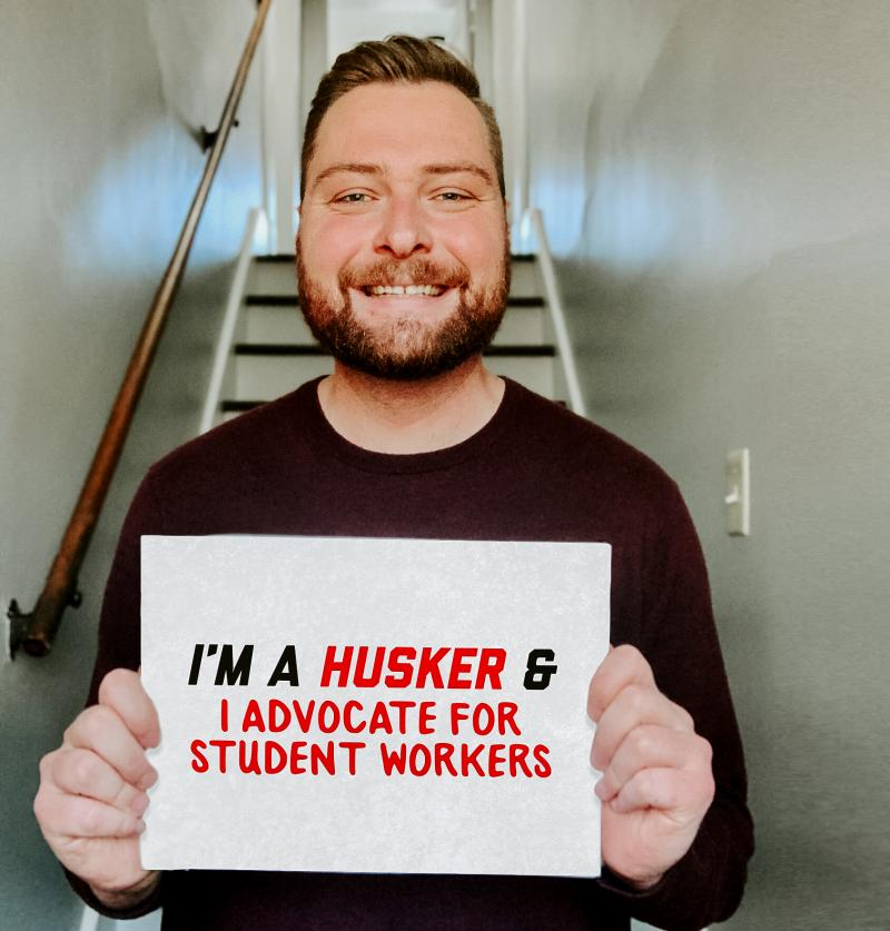 """Roger holding a sign that says """"I'm a Husker and I advocate for student workers."""""""