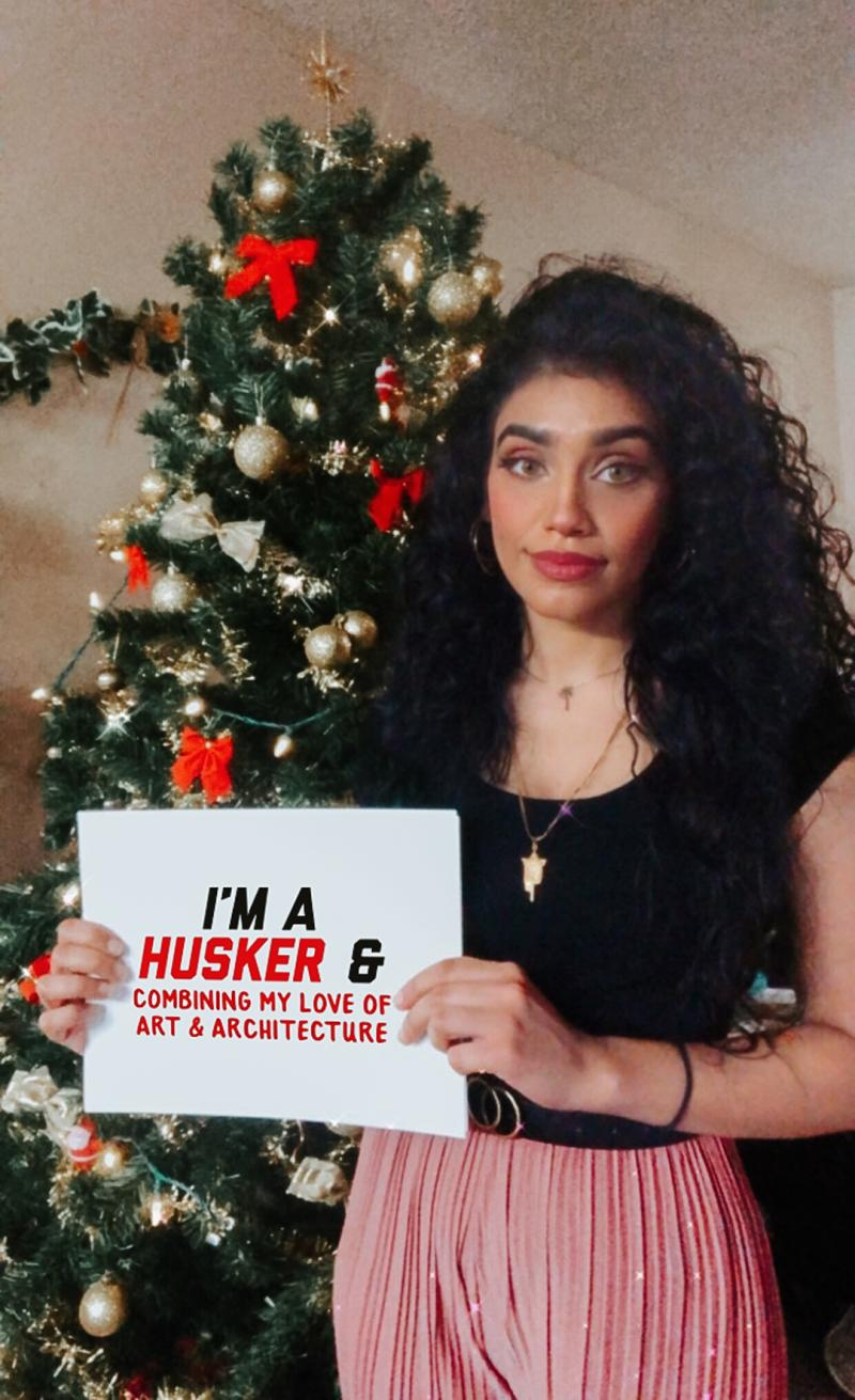 """Samah holding a sign that says """"I'm a Husker and combining my love of art and architecture."""""""