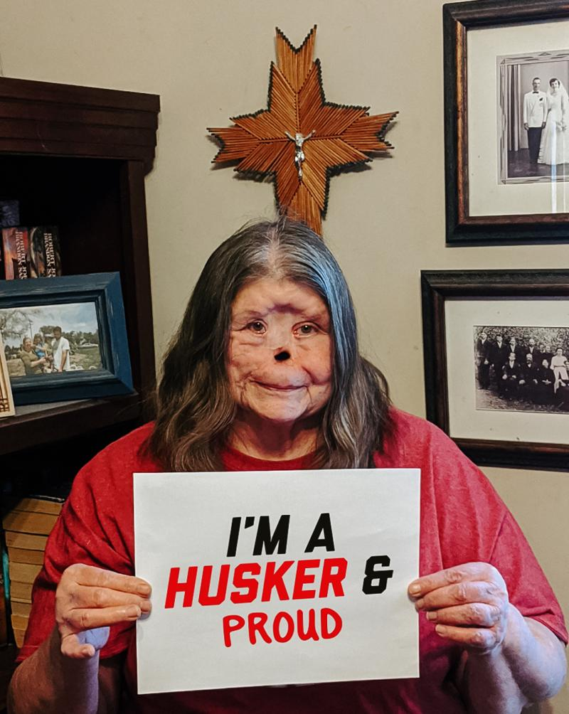 """Susan smiles in her home holding a sign that says """"I'm a Husker & Proud"""""""