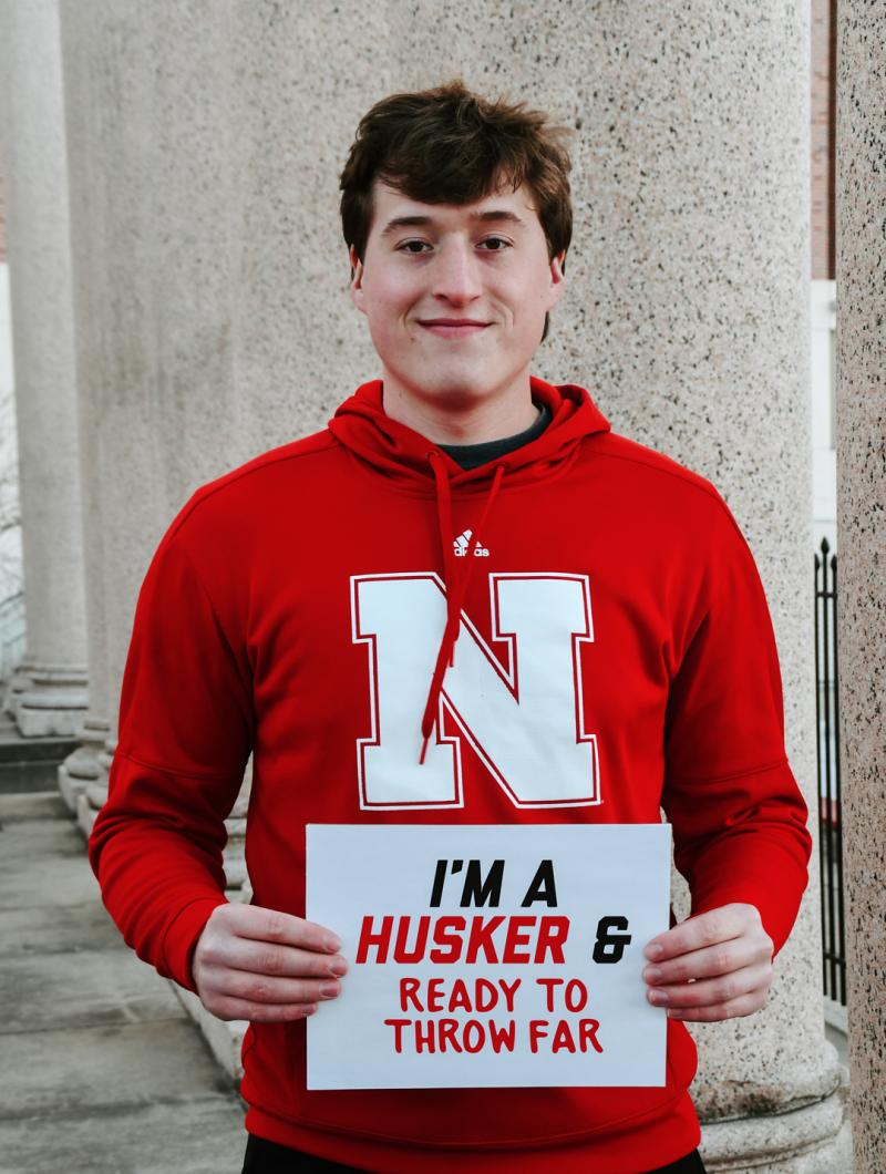 """Tyler smiles holding a sign that says """"I'm a Husker & ready to throw far"""""""