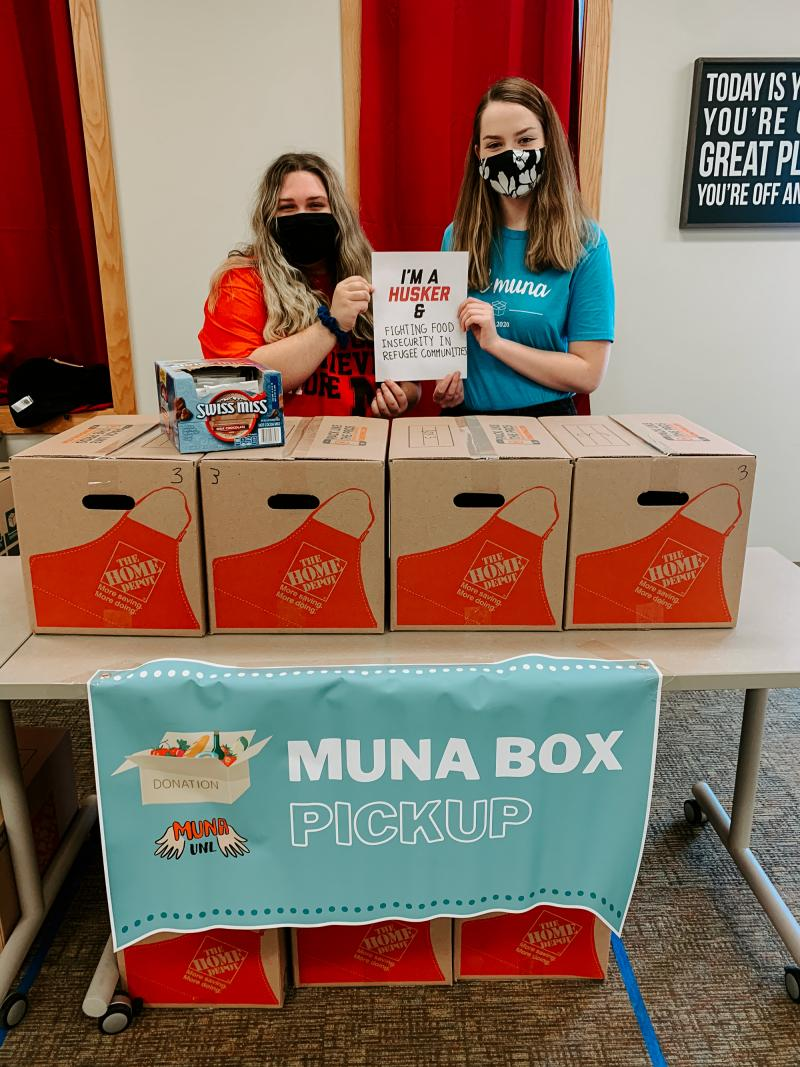 """Makayla and Kaitlin stand with boxes of donations as they hold a sign that says """"I'm a Husker & fighting food insecurity in refugee communities"""""""