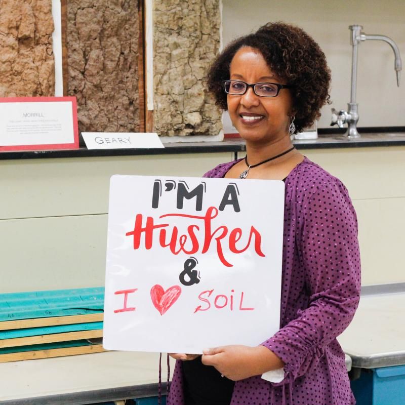 Professor holding I am a Husker sign with statement