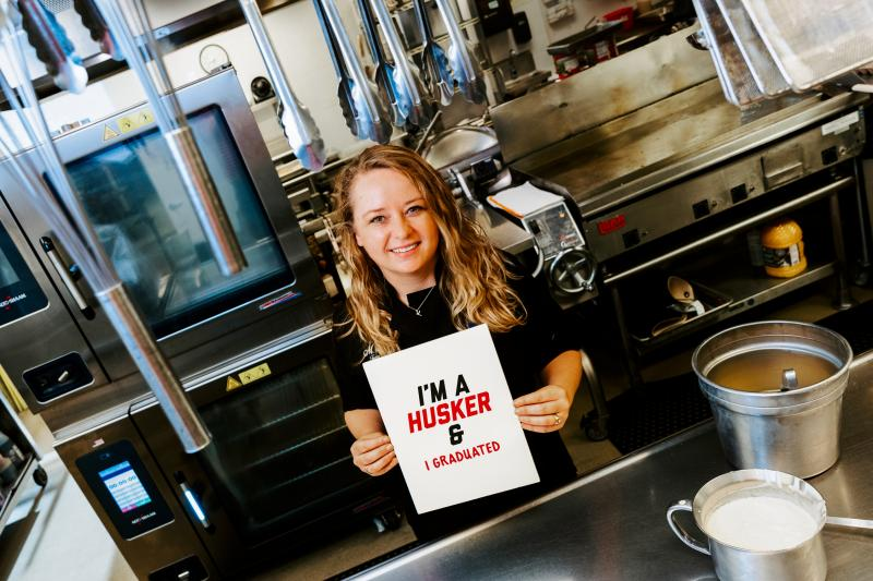 """Misty poses for a photo in the kitchen she's worked for over 2 decades. She holds a sign that says """"I'm a Husker & I graduated"""""""