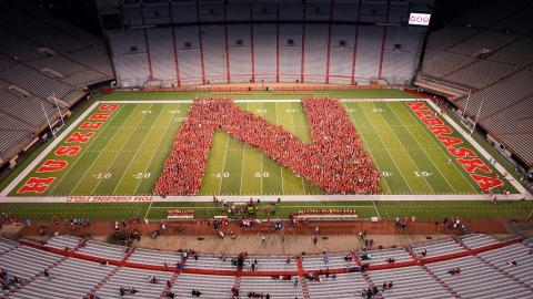 "photo of new students gathered on memorial stadium field in the shape of an ""N"""