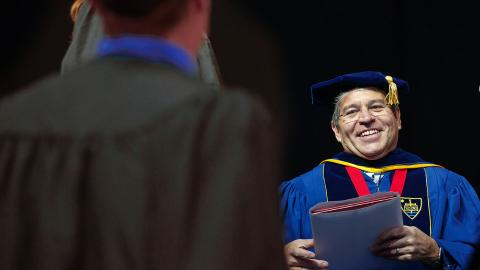 Lance C. Pérez prepares to hand a diploma to a Nebraska Engineering student during the undergraduate commencement ceremony on May 5. Pérez has been named dean of engineering.