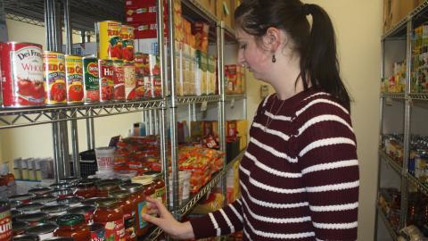 Graduate student Jessica Lanctot restocks the pantry shelf with pasta sauce.