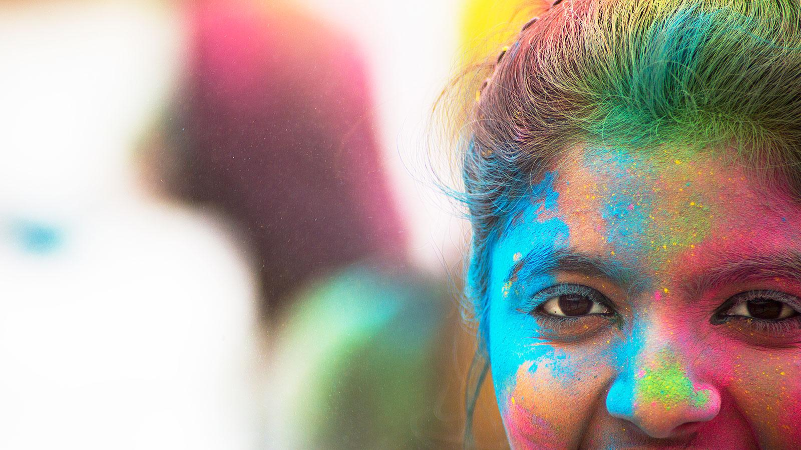 Women's face covered in colorful powders